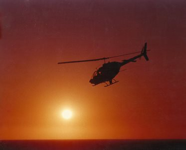 Bell 206B-1 helicopter flying off into the sunset.